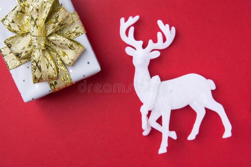 Boîte-cadeau élégant enveloppé en papier argenté attaché avec les cerfs communs blancs d'arc d'or de ruban sur le fond rouge fonc photographie stock
