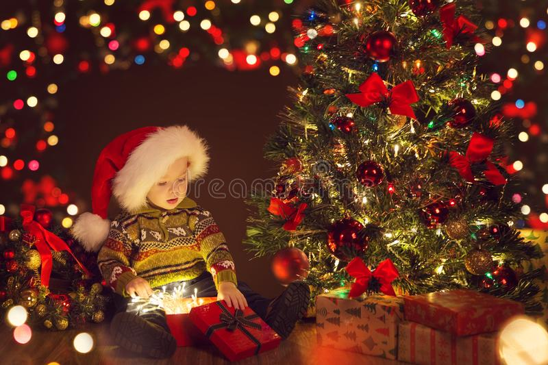 Boîte-cadeau actuel ouvert de bébé de Noël sous l'arbre de Noël, enfant heureux photographie stock