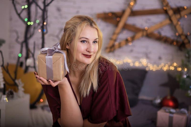 Boîte-cadeau actuel ouvert de femme de Noël dans la chambre de Noël, arbre de vacances image libre de droits