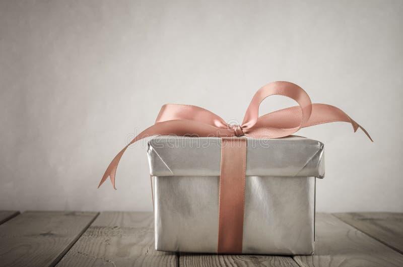 Boîte-cadeau argenté avec l'effet d'arc et de vintage photographie stock
