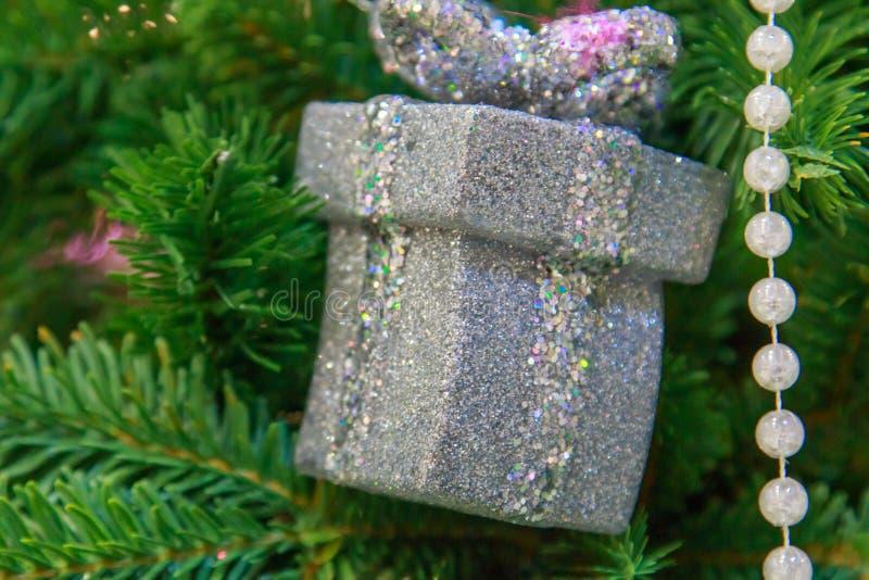 Boîte-cadeau argenté sur la fin d'arbre de nouvelle année photos stock