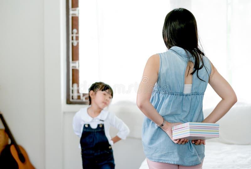 Boîte-cadeau asiatique de peau de mère derrière elle de nouveau à la surprise la fille dans la chambre à coucher image stock