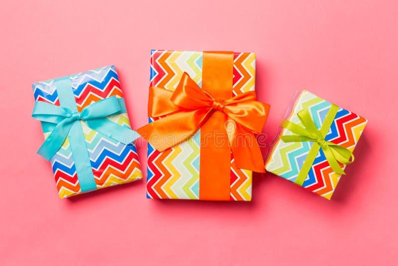 Boîte-cadeau avec arc bleu, vert et orange pour Noël ou le Nouvel An sur fond corallien vivant, vue du haut photographie stock
