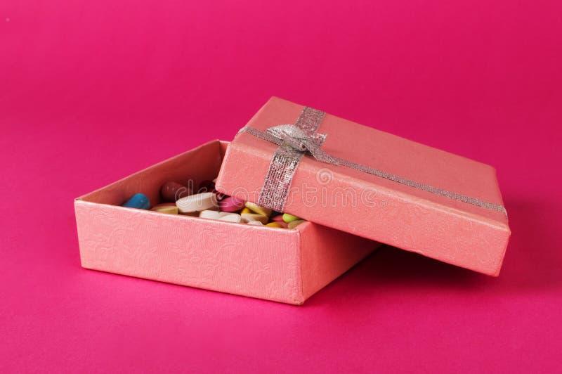 Boîte-cadeau avec des pilules sur un backgroung rose Concept actuel de médecine photos stock