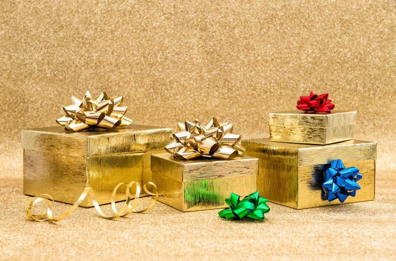 Boîte-cadeau avec l'arc de ruban au-dessus du fond d'or photos stock