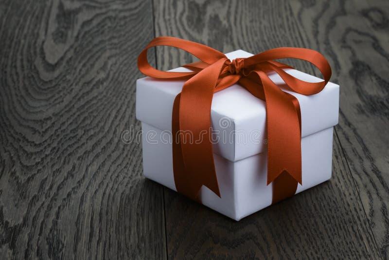 Boîte-cadeau avec l'arc de ruban sur la vieille table de chêne image stock