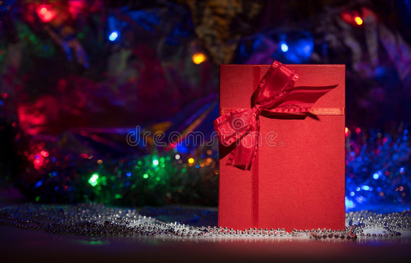 Boîte-cadeau avec l'arc rouge sur le fond abstrait photo stock