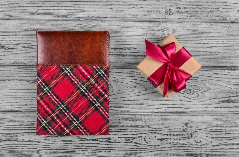 Boîte-cadeau avec le ruban de satin et bloc-notes dans une cage sur un fond gris Copiez l'espace images libres de droits