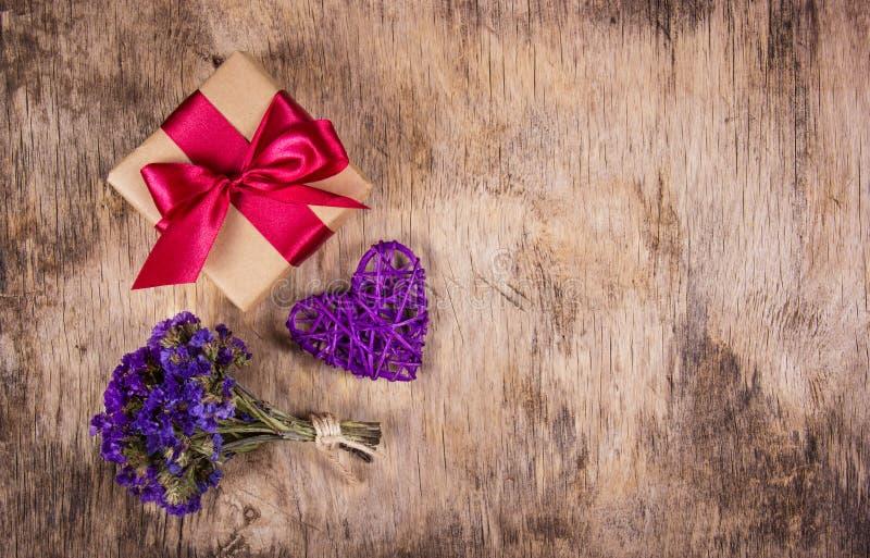 Boîte-cadeau avec le ruban de satin, le coeur en osier et les fleurs sur un vieux fond en bois Copiez l'espace images libres de droits