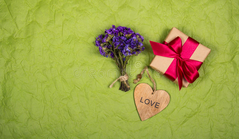 Boîte-cadeau avec le ruban de satin, les fleurs sauvages et le coeur Cadeaux sur un fond vert de papier Copiez l'espace photos libres de droits