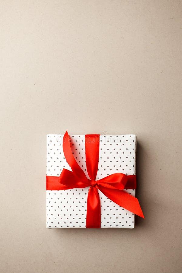 Boîte-cadeau avec le ruban rouge sur le fond gris Fête des mères de Valentine, vente, concept d'anniversaire photo libre de droits