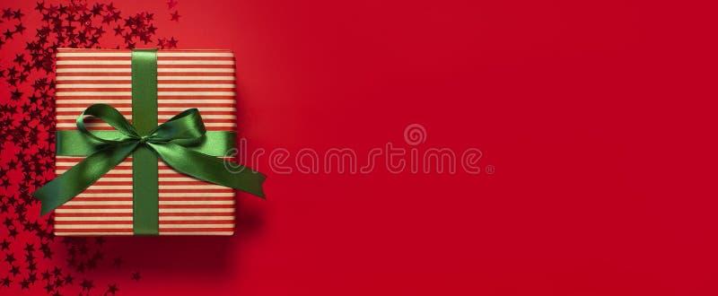 Boîte-cadeau avec le ruban vert et la forme olographe de confettis de scintillement d'étoiles sur la configuration plate rouge de photo stock