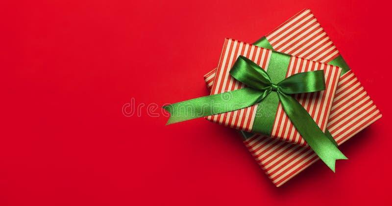Boîte-cadeau avec le ruban vert sur la configuration rouge d'appartement de vue supérieure de fond Le concept de vacances, nouvel photographie stock