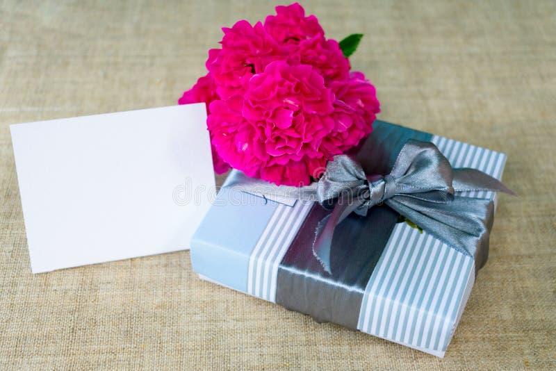 Boîte-cadeau avec le sac de ruban et fleurs roses sur le fond beige Carte avec le fond floral de fleurs sensibles avec l'espace d images stock