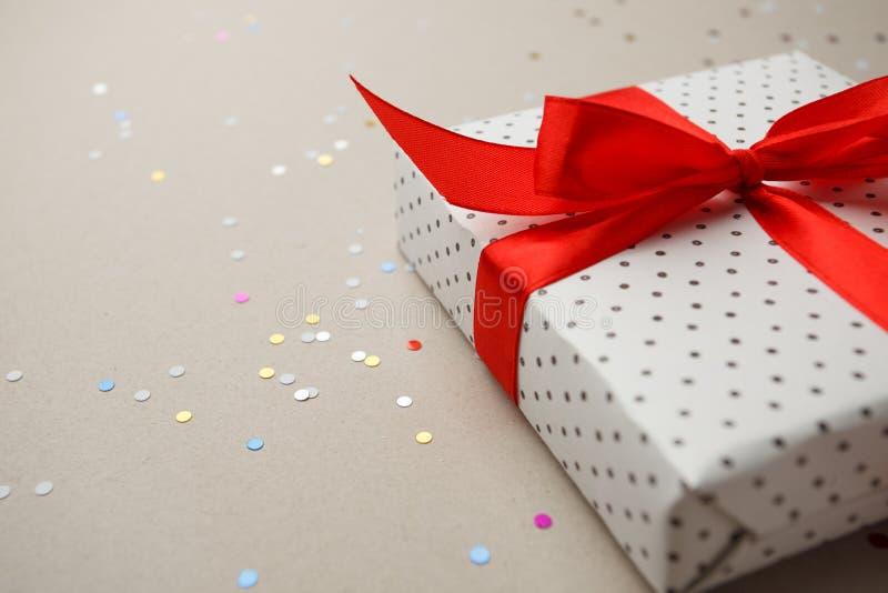 Boîte-cadeau avec les confettis rouges de ribbonand sur le fond gris Fête des mères de Valentine, vente, concept d'anniversaire photographie stock libre de droits