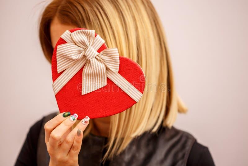 Boîte-cadeau avec un ruban dans des mains femelles Le concept convient aux histoires d'amour, aux anniversaires et au Valenti image stock