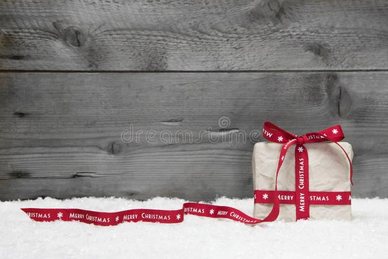 Boîte-cadeau blanc avec le long ruban rouge et arc sur le backg en bois gris photos stock