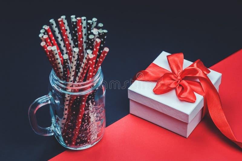 Boîte-cadeau blanc avec le ruban rouge et les pailles de papier photographie stock libre de droits