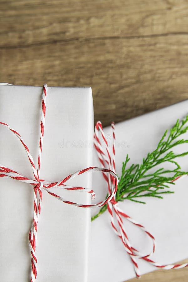 Boîte-cadeau blancs élégants attachés avec la brindille rouge de genévrier de vert de ruban empilée sur le fond de table en bois  photo libre de droits