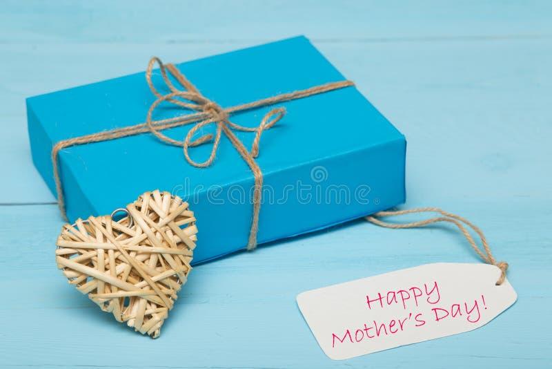 Boîte-cadeau bleu avec le coeur de paille et la carte de jour de mères photographie stock libre de droits
