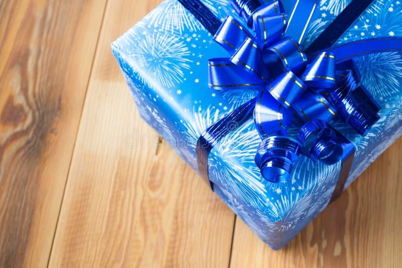 Boîte-cadeau bleu avec le ruban bleu-foncé sur le Tableau en bois image stock