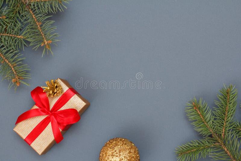 Boîte-cadeau, branches d'arbre de sapin et boule de Noël sur le fond gris photos libres de droits