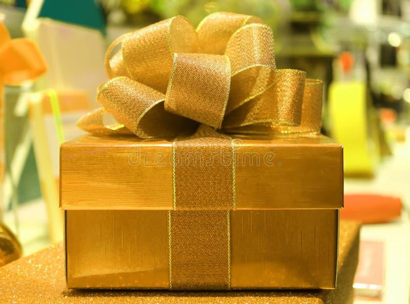 Boîte-cadeau brillant carré d'or avec l'arc de ruban d'or de scintillement, fond brouillé photos libres de droits