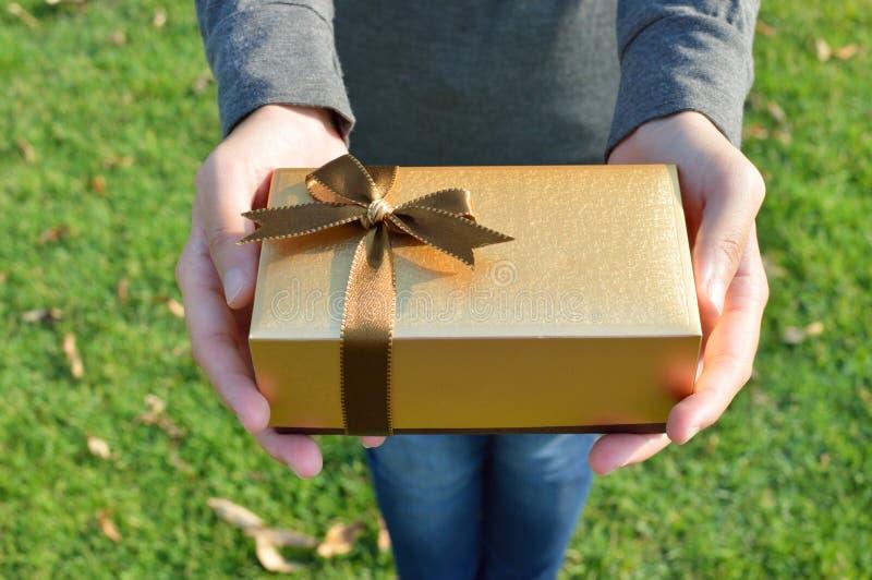 Boîte-cadeau chez les mains de la femme photos stock
