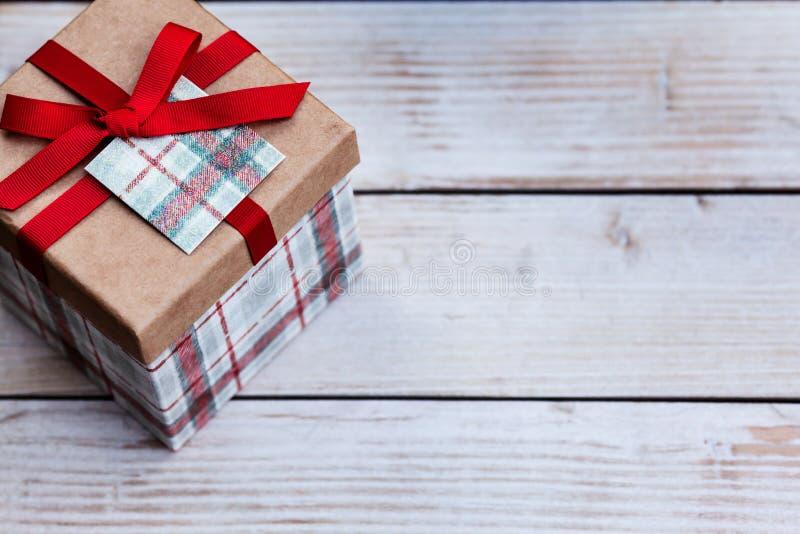 Boîte-cadeau chic de Noël sur un fond en bois avec l'espace de copie du côté droit, concept de vacances de saison photo libre de droits