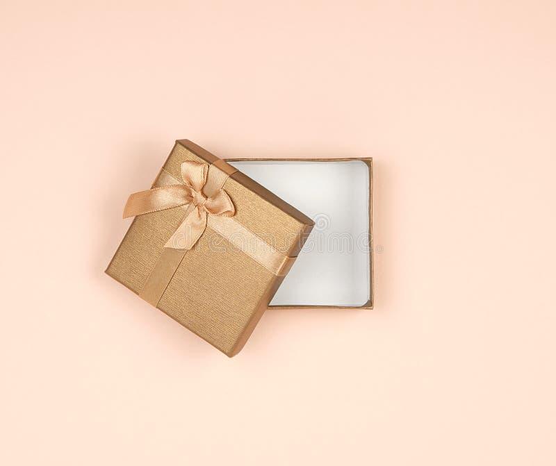 boîte-cadeau d'or ouvert avec un arc sur un fond beige image stock