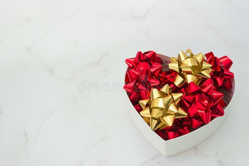 Boîte-cadeau de coeur avec les arcs de fête à l'intérieur sur le fond de marbre blanc, foyer sélectif, l'espace de copie Thème d' photographie stock libre de droits