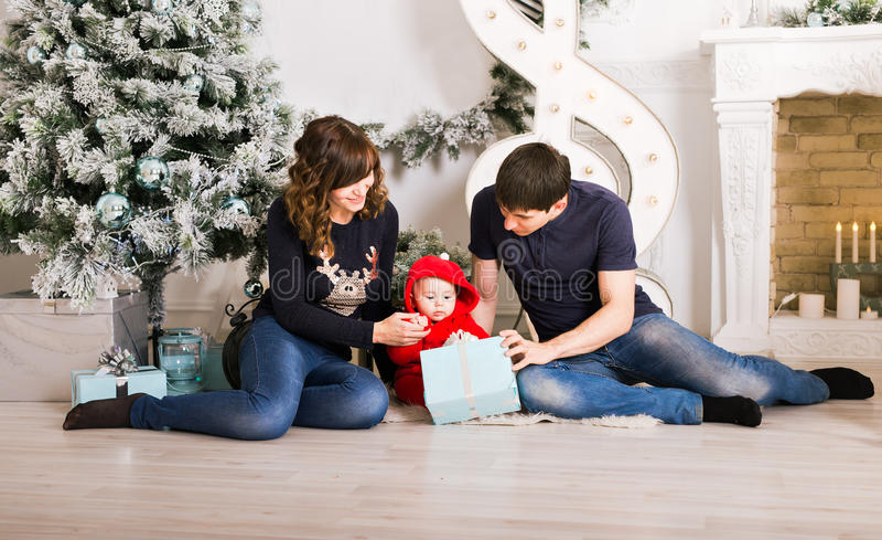 Boîte-cadeau de famille de Noël, père de mère et enfant actuels ouverts de bébé dans la chambre décorée, se reposant sous l'arbre photographie stock libre de droits