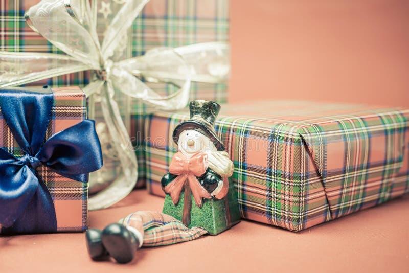 Boîte-cadeau de Noël avec le jouet de bonhomme de neige au fond rouge photos stock