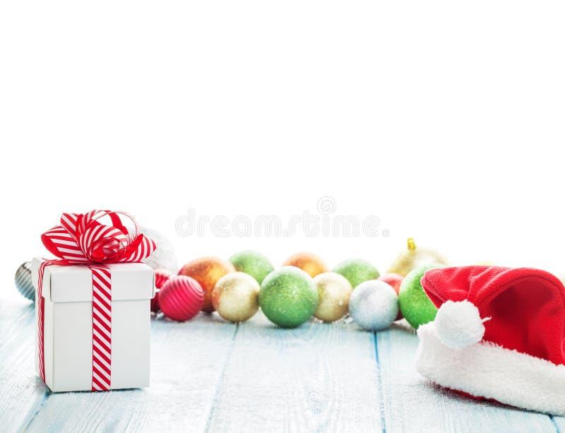 Boîte-cadeau de Noël, chapeau de Santa et babioles colorées photo libre de droits