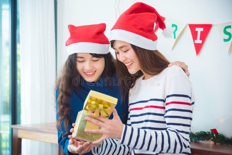 Boîte-cadeau de Noël d'ouverture d'amie en partie images stock