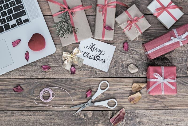 Boîte-cadeau de Noël et ordinateur cultivé sur le fond en bois de vintage images stock
