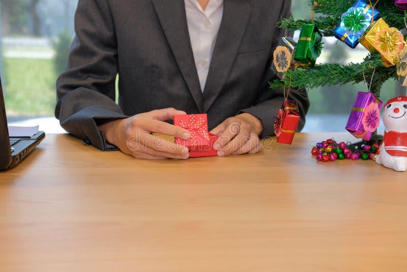 boîte-cadeau de nouvelle année de Noël d'ouverture d'homme d'affaires sur le lieu de travail photo libre de droits