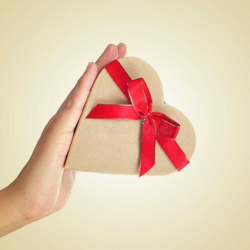 Boîte-cadeau en forme de coeur dans la main d'un homme images libres de droits