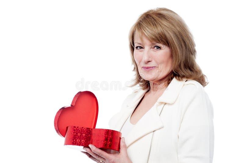 Boîte-cadeau en forme de coeur s'ouvrant de Madame photo stock