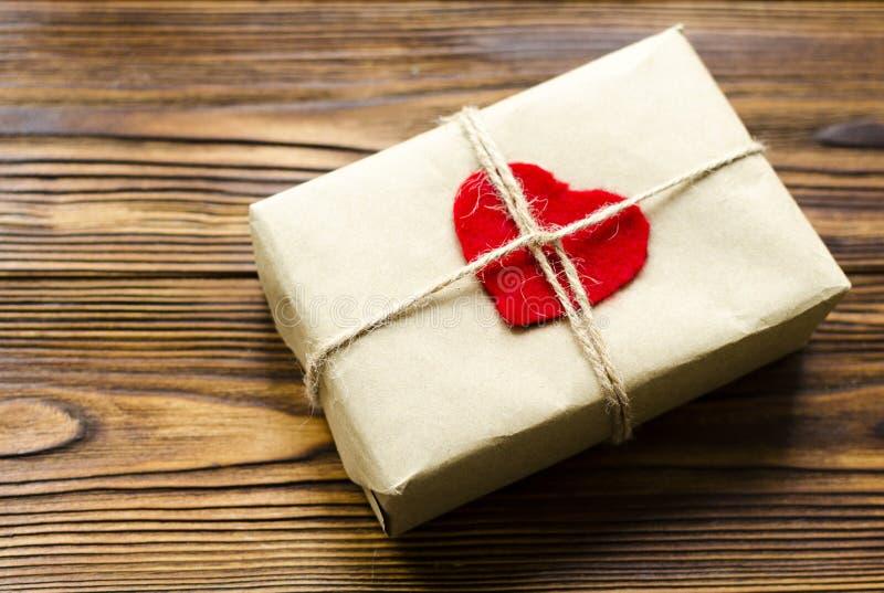Boîte-cadeau enveloppé au papier d'emballage et au coeur en bois rouge sur t en bois photo libre de droits