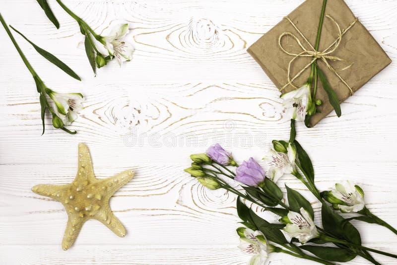 Boîte-cadeau enveloppé dans le papier, la fleur et les étoiles de mer de métier sur un dessus de table blanc Configuration plate  photos stock