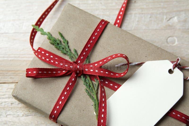 Boîte-cadeau, enveloppé dans le papier réutilisé, l'arc rouge et l'étiquette sur le CCB en bois image stock