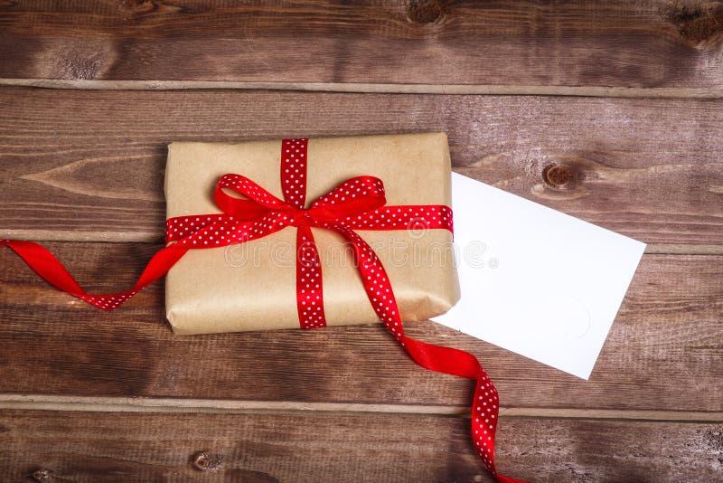 Boîte-cadeau enveloppé de vintage avec l'arc rouge de ruban et carte cadeaux sur la table en bois photographie stock
