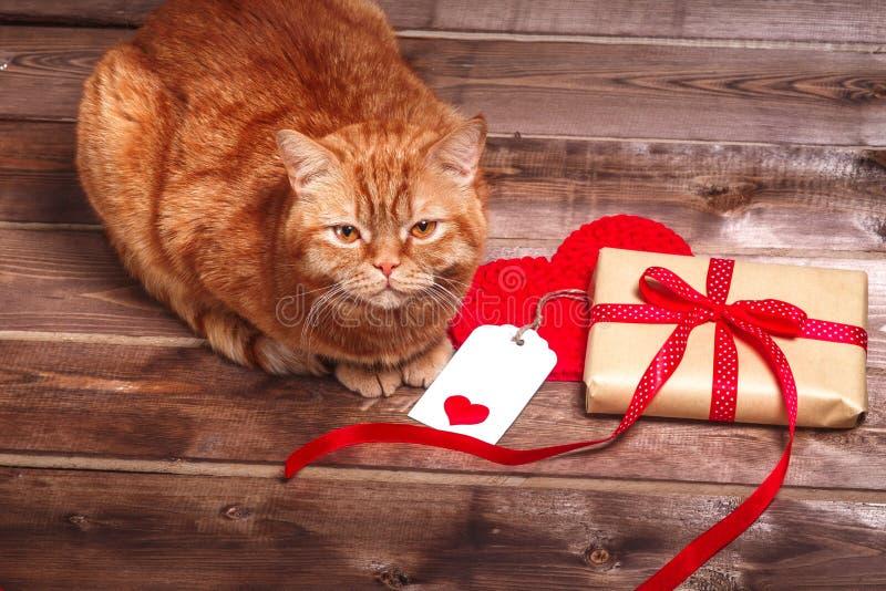 Boîte-cadeau enveloppé de vintage avec l'arc rouge de ruban et carte cadeaux sur la table en bois photo libre de droits