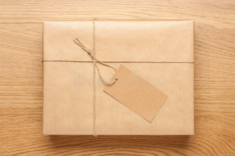 Boîte-cadeau enveloppé en papier d'emballage sur la table en bois photographie stock