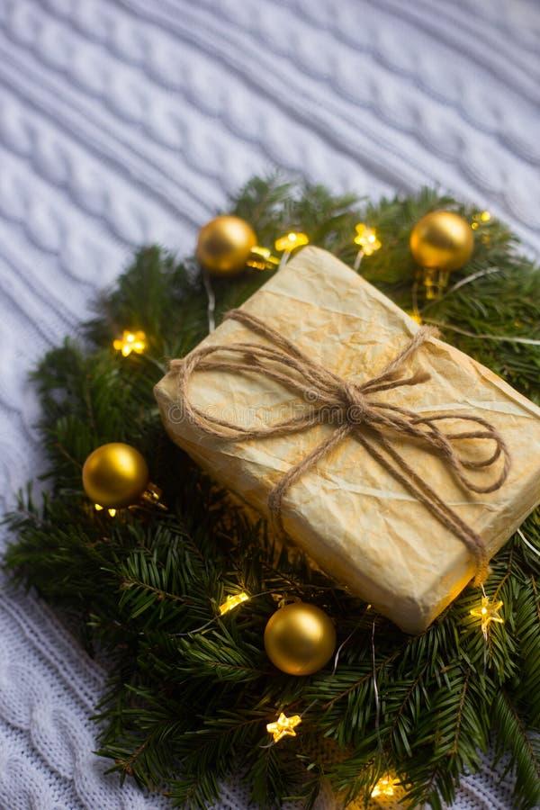 Boîte-cadeau enveloppé près de la guirlande de sapin décorée des boules d'or de Noël et lovée avec la guirlande rougeoyante avec  photos stock