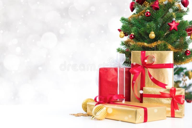 Boîte-cadeau et arbre de Noël décoré coloré sur le bokeh blanc images libres de droits