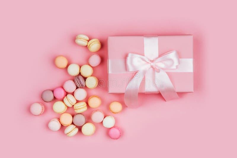 Boîte-cadeau et macarons sur le fond rose photos libres de droits