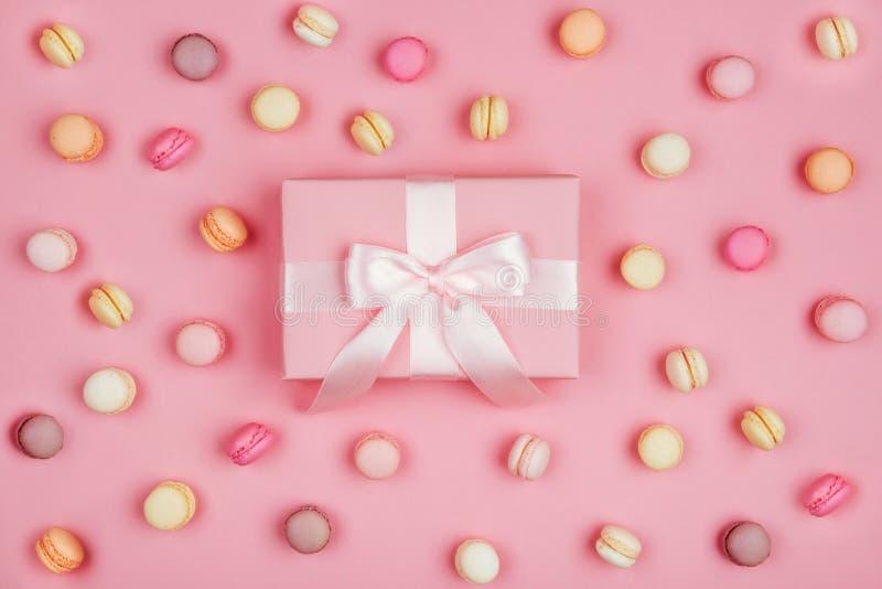 Boîte-cadeau et macarons sur le fond rose images stock