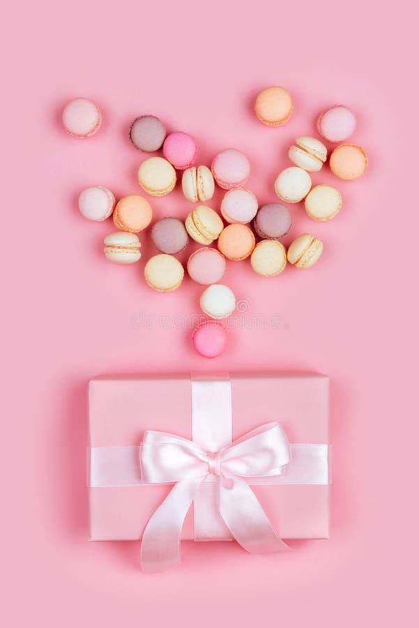 Boîte-cadeau et macarons sur le fond rose photographie stock